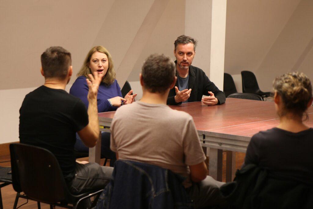 Pięć osób siedzi przy dużym kwadratowym stole w jasnej sali o lekko skośnych ścianach. Kobieta i dwóch mężczyzn usytuowani są plecami do obiektywu. Pozostała dwójka – prowadzący i tłumaczka PJM – siedzą przodem. Po ich minach można się domyślić, że prowadzą wciągającą, intrygującą, a może też zabawną rozmowę.