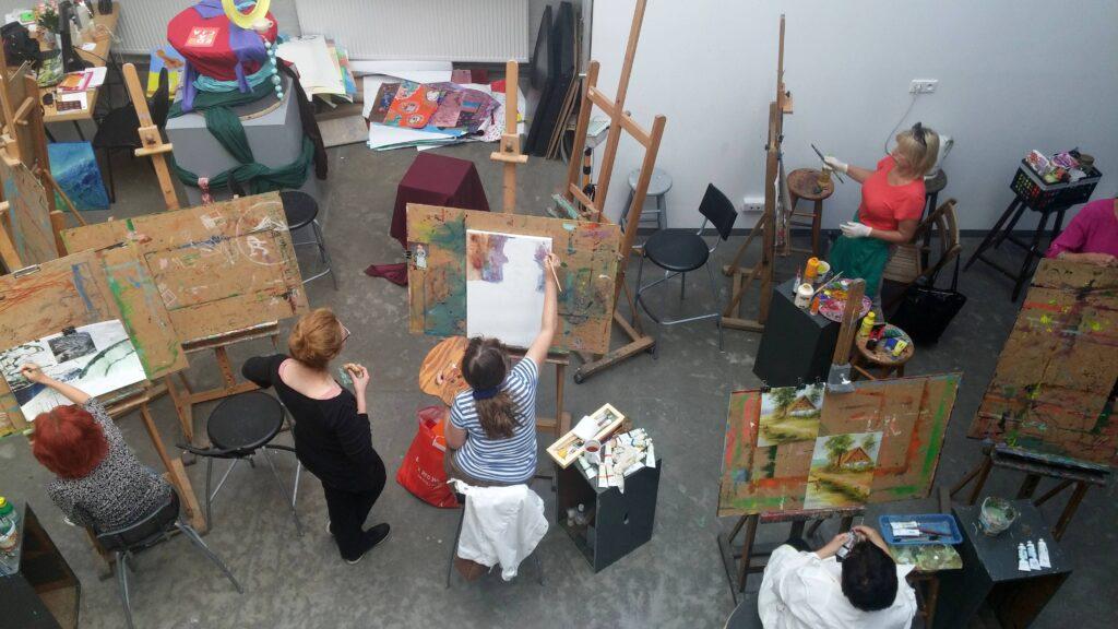 Ujęcie pracowni z góry. Pięć osób pracujących przy sztalugach, dwie panie dyskutują o jednej z prac. Z boku, przygotowana martwa natura i leżący na podłodze plik prac.
