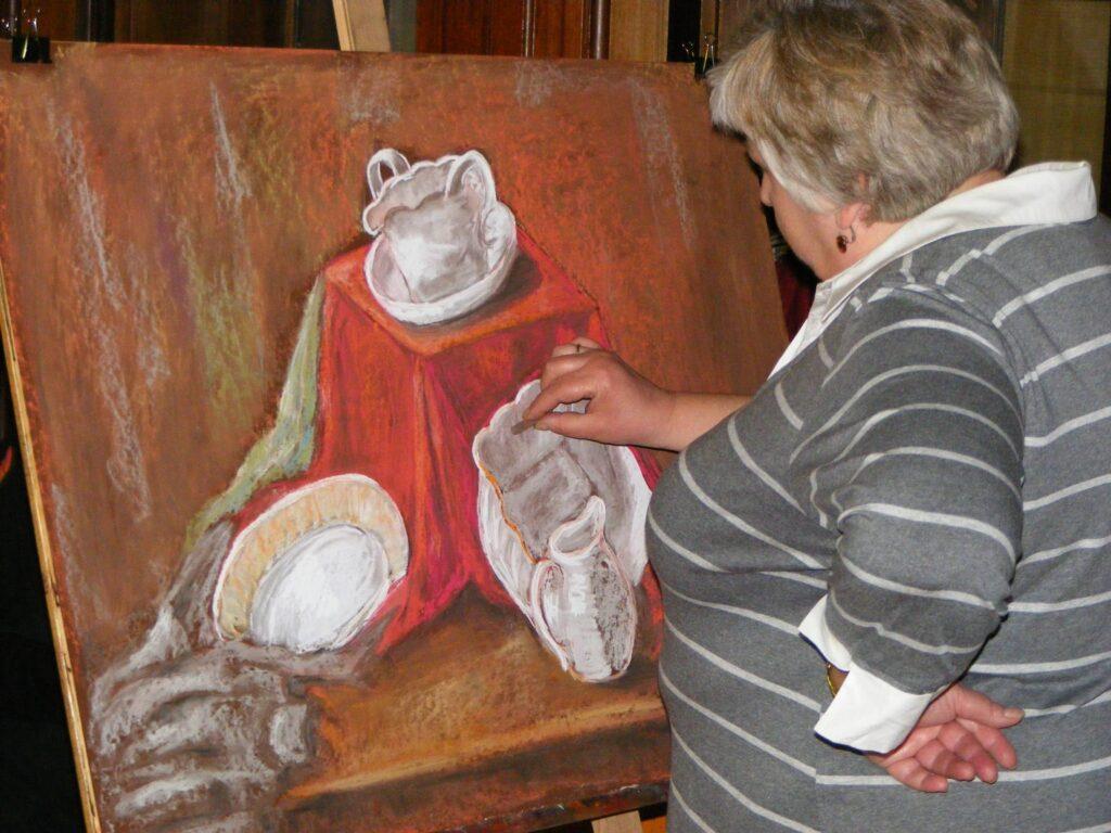 Kobieta stojąca bokiem przy sztaludze dokańcza obraz w technice pasteli suchych przedstawiający martwą naturę – cztery naczynia z białej porcelany.