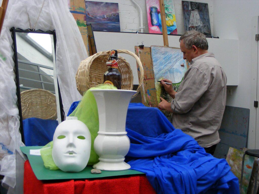 Na pierwszym planie znajduje się przygotowana do pracy martwa natura – maska, wazon, lustro, kosz i butelka. Na drugim planie, mężczyzna rysujący przy sztaludze pejzaż.