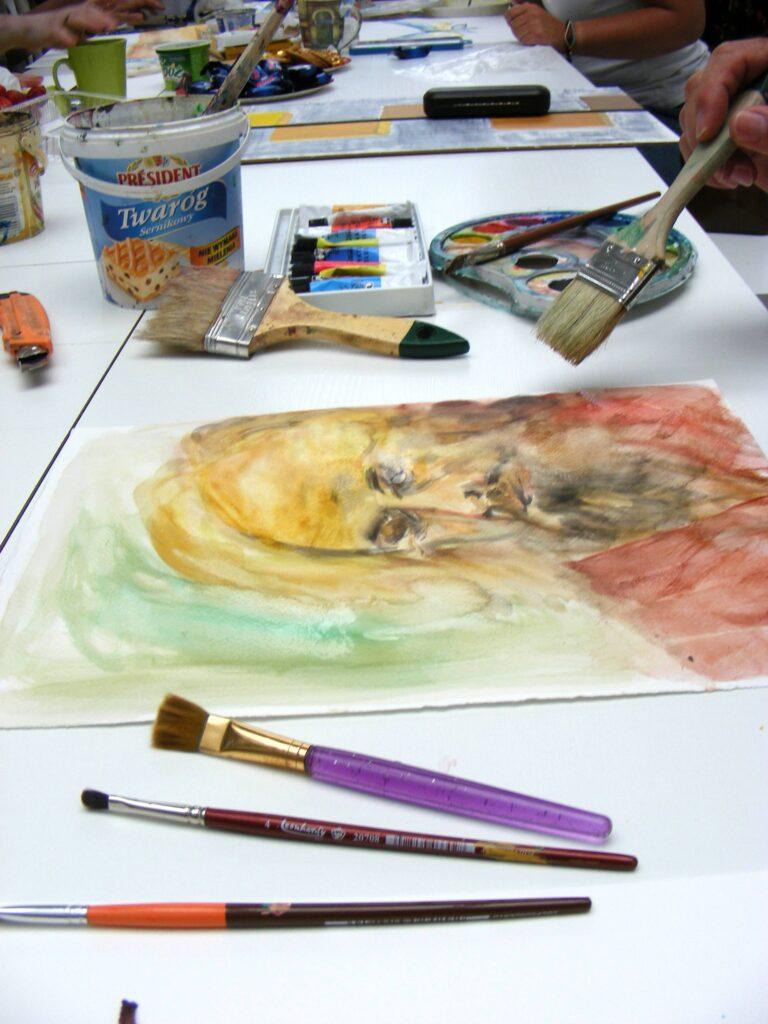 Blat stołu, na którym są trzy stanowiska pracy uczestników pracowni. Na pierwszoplanowym stanowisku leży portret mężczyzny, pędzle, farby, paleta do mieszania farb i wiaderko z wodą. Widać rękę uczestnika, która trzyma pędzel.