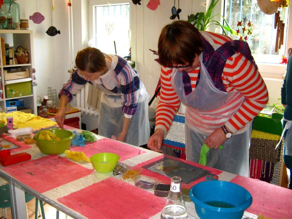 Dwie kobiety pochylają się nad stołem warsztatowym, wykonują one arkusze papieru czerpanego. Na stole, poza pracami, stoją również miski z wodą.