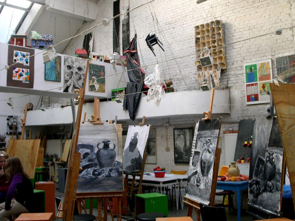 W dolnej części zdjęcia znajdują się cztery prace oparte o sztalugi, przedstawiające martwą naturę z dzbanem, widoczną pomiędzy sztalugami. W górnej części zdjęcia ekspozycja prac  podwieszonych pod sufitem, zarówno malarskich, rysunkowych, jak i przestrzennych
