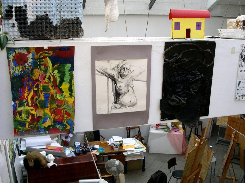 Zdjęcie pracowni wykonane z góry. Na pierwszym planie znajdują się trzy prace podwieszone do sufitu. Od lewej: abstrakcyjne malarstwo w bardzo intensywnych kolorach, rysunek nagiego mężczyzny od pasa w górę, trójwymiarowa praca wykonana z papieru i sznura w czarnym kolorze.