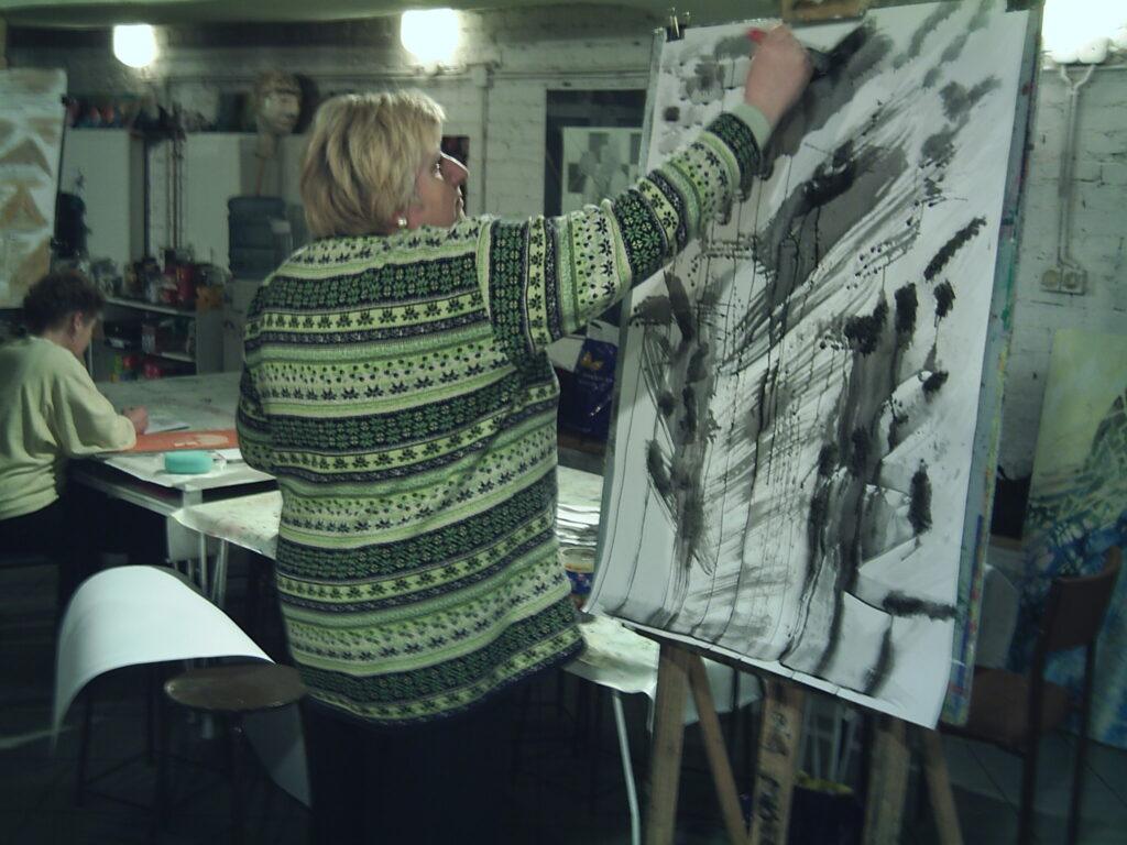 Kobieta stojąca przy sztaludze, tworząca abstrakcyjną kompozycję węglem. Na dalszym planie, dziewczynka, rysująca coś siedząc przy stole.