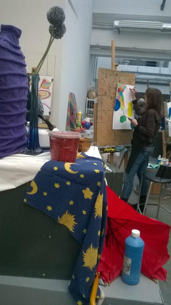 Kompozycja martwej natury: tkaniny, farby, miska, wazon z kwitnącym czosnkiem i czajnik. Za nią młoda dziewczyna maluje coś, stojąc przy sztaludze.
