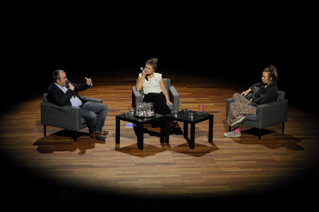 W Sali Wielkiej w CK ZAMEK na szarych krzesłach oddalonych w bezpieczniej odległości siedzą Bogdan Chojnicki, Anna Pięta oraz Areta Szpura. Cała trójka oświetlona jest ciepłym światłem reflektora, reszta sali okryta jest ciemnością. Pan Bogdan w jednej dłoni trzyma mikrofon, drugą gestykuluje. Anna i Areta przysłuchują się mu z ciekawością.