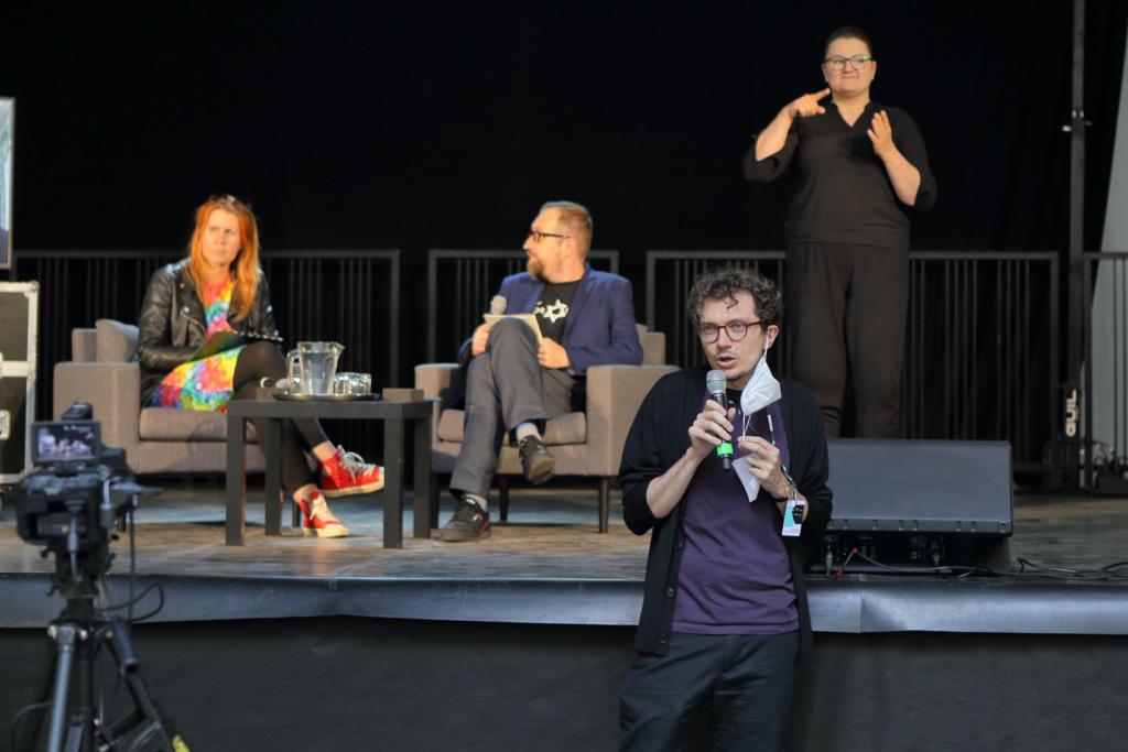Na pierwszym planie przed kamera stoi Jakub z mikrofonem. Za nim, na scenie znajdują się trzy osoby: gestykulująca Marta – tłumaczka PJM oraz siedzący na fotelach: Michał – prowadzący rozmowę oraz gościni Marta.
