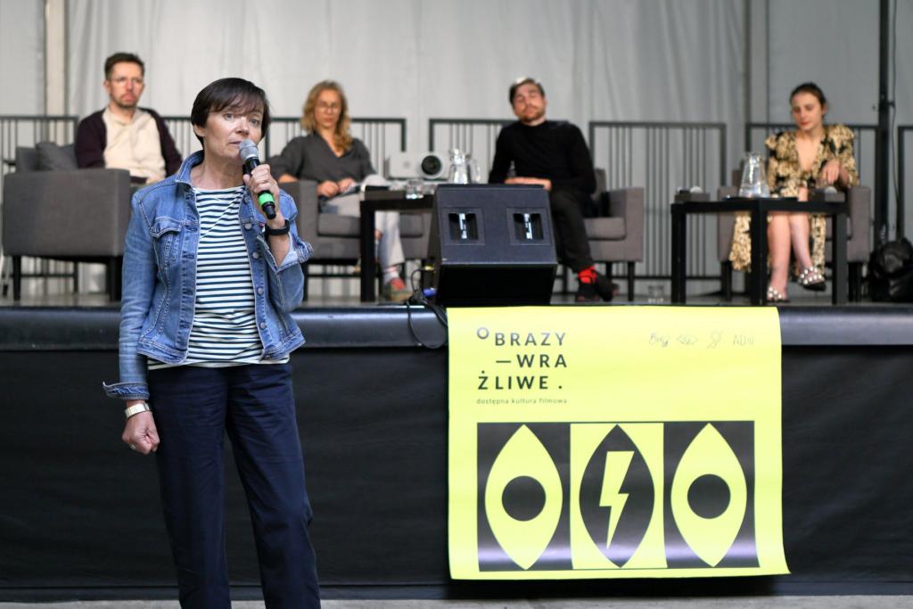 """Na pierwszym planie Anna Hryniewiecka – dyrektorka ZAMKU, stoi przed sceną, w ręku trzyma mikrofon. Obok niej wisi żółto-czarny plakat """"Obrazów wrażliwych"""". W tle, na scenie widoczne są osoby zaproszone do dyskusji."""