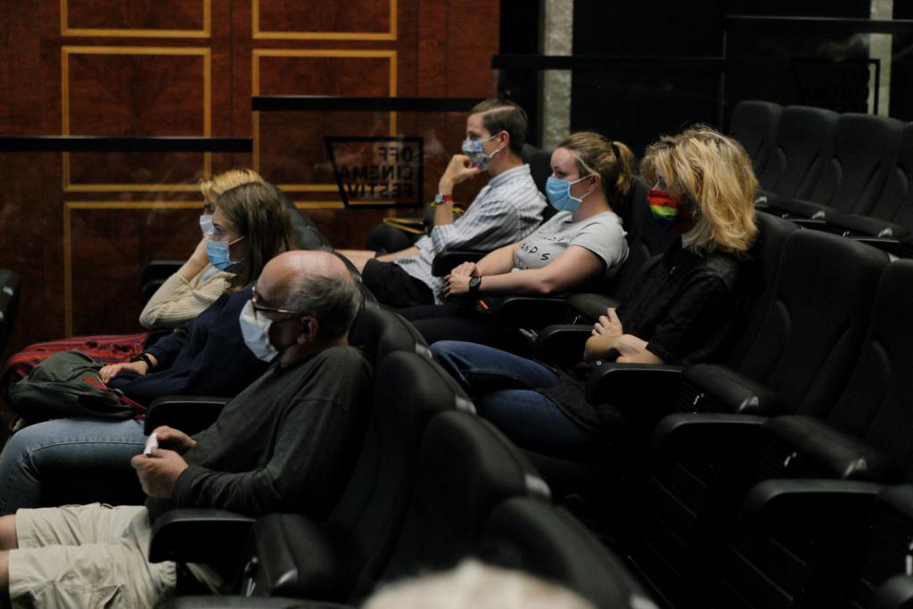 Zbliżenie na publiczność, 6 osób (4 kobiety i 2 mężczyzn) siedzi na kinowych fotelach, w dwóch rzędach, zachowują odległość, mają maseczki na twarzach.