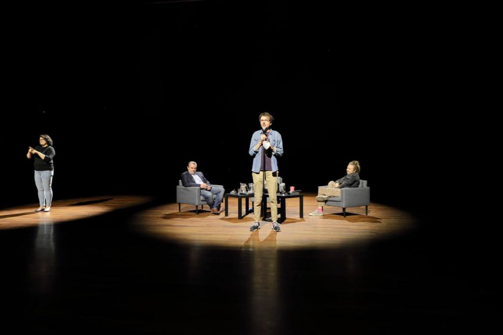 Spowita ciemnością Sala Wielka, a na niej dwa rozświetlone miejsca: pierwsze, po środku sali, gdzie stoi Jakub Walczyk z mikrofonem w ręce, a za nim widać siedzących na szarych fotelach zaproszonych do dyskusji Bogdana Chojnickiego i Aretę Szpurę. W drugim oświetlonym punkcie stoi Marta Jaroń i tłumaczy słowa Jakuba na PJM.