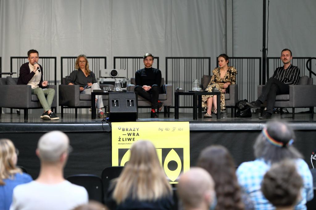 """Na scenie, na szarych fotelach siedzą (od lewej): Bartek (z mikrofonem w dłoni), Zofia, Zenek, Aleksandra i Mateusz. Do sceny, na środku, został przytwierdzony żółto-czarny plakat """"Obrazów wrażliwych"""". Na dole zdjęcia (widoczne od tyłu) rozmazane głowy uczestniczek i uczestników dyskusji."""