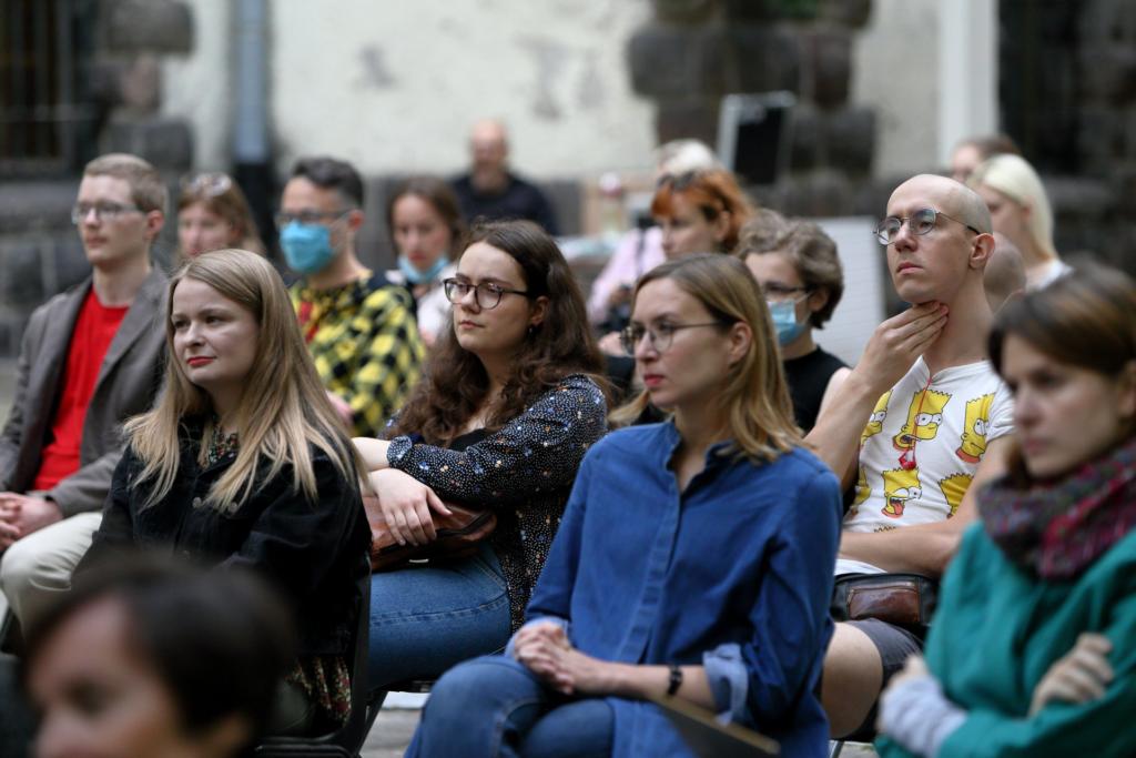 Zbliżenie na publiczność. Niektóre osoby mają założone maseczki, siedzą na krzesełkach na dziedzińcu zamkowym.