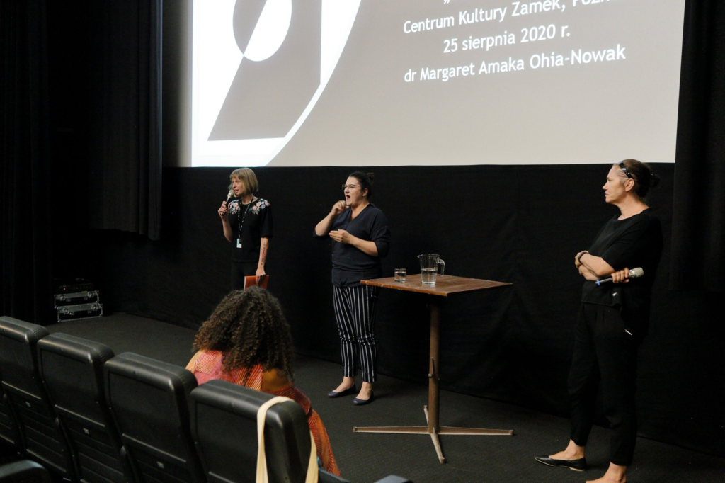 Trzy kobiety stoją przed ekranem kinowym, na którym widać fragment planszy zapowiadającej wydarzenie (możemy przeczytać m.in. nazwisko prowadzącej wykład dr Margaret Amaka Ohia-Nowak). Ewelina mówi do mikrofonu, Marta Jaroń tłumaczy na polski język migowy, Joanna patrzy w ich kierunku. W pierwszym rzędzie siedzi Margaret (odwrócona plecami do fotografa).