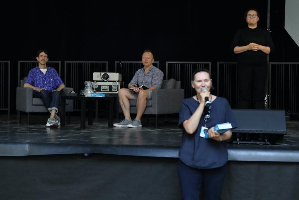 """Przed sceną stoi Joanna Przygońska. W jednej ręce trzyma mikrofon, a w drugiej książkę """"Najlepsze miasto świata"""". Za nią, na scenie, po prawej stronie stoi Marta, tłumaczka PJM, zaś z lewej strony siedzą, na szarych fotelach, autor książki Grzegorz Piątek oraz prowadzący rozmowę Jakub Głaz."""
