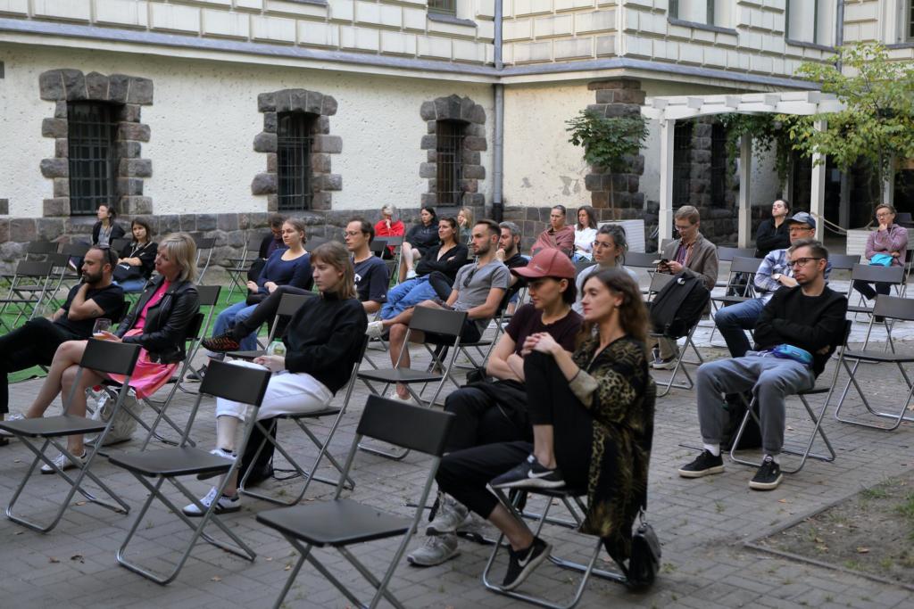 Na Dziedzińcu Zamkowym na rozstawionych w bezpiecznej odległości krzesłach siedzi duża grupa osób przysłuchujących się dyskusji.