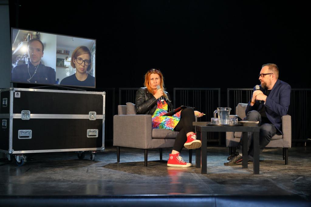 Po lewej stronie sceny na czarnych skrzyniach stoi duży ekran, na którym ukazane są twarze Jana Komasy i Anny Mazurczak połączonych online. Po prawie stronie zdjęcia siedzą na szarych fotelach Marta Florkiewicz-Borkowska oraz Michał Nogaś. Na zdjęciu wyróżniają się czerwone trampki Marty.