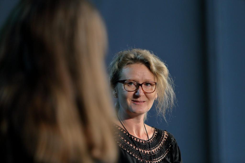 Na głównym planie blondwłosa kobieta w okularach – Iza Klementowska – ujęta od piersi w górę.