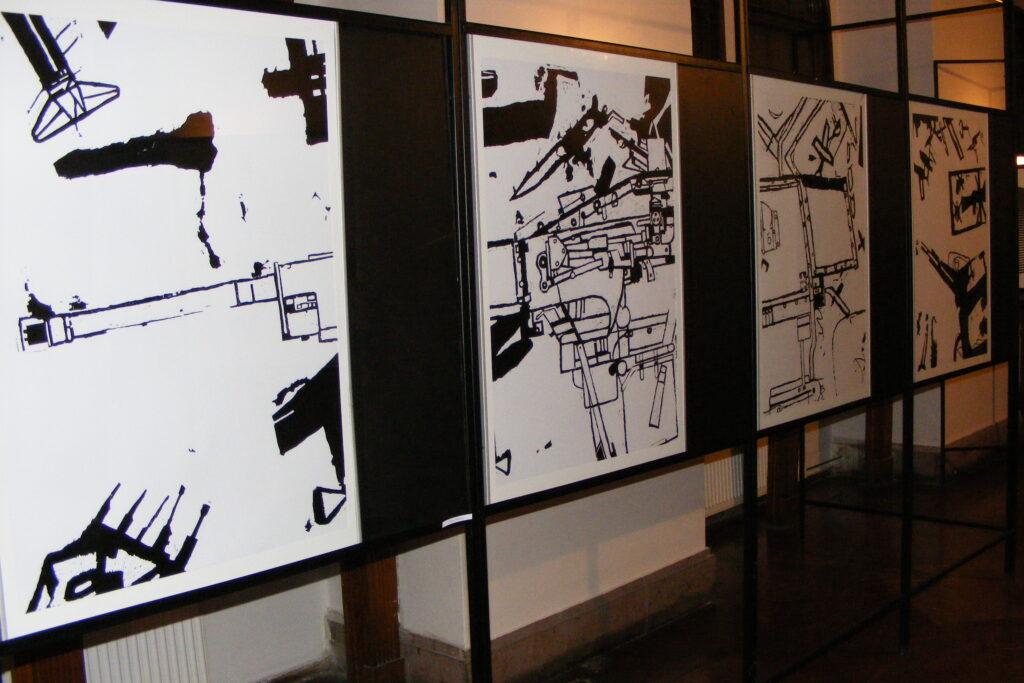 Cztery prace graficzne na stelażach wystawienniczych, przedstawiające w czarnym kolorze przedmioty i maszyny mechaniczne.