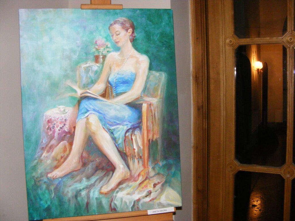 Obraz prezentowany tuż przy szklanych drzwiach, przedstawiający czytającą młodą kobietę siedzącą na fotelu, przy którym stoi mały stolik z filiżanką.