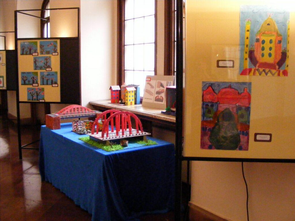 Wystawa prac dziecięcych. Kilka małych prac płaskich oraz, w centralnym miejscu, stół z pracami przestrzennymi – projekty dwóch mostów oraz budynków.