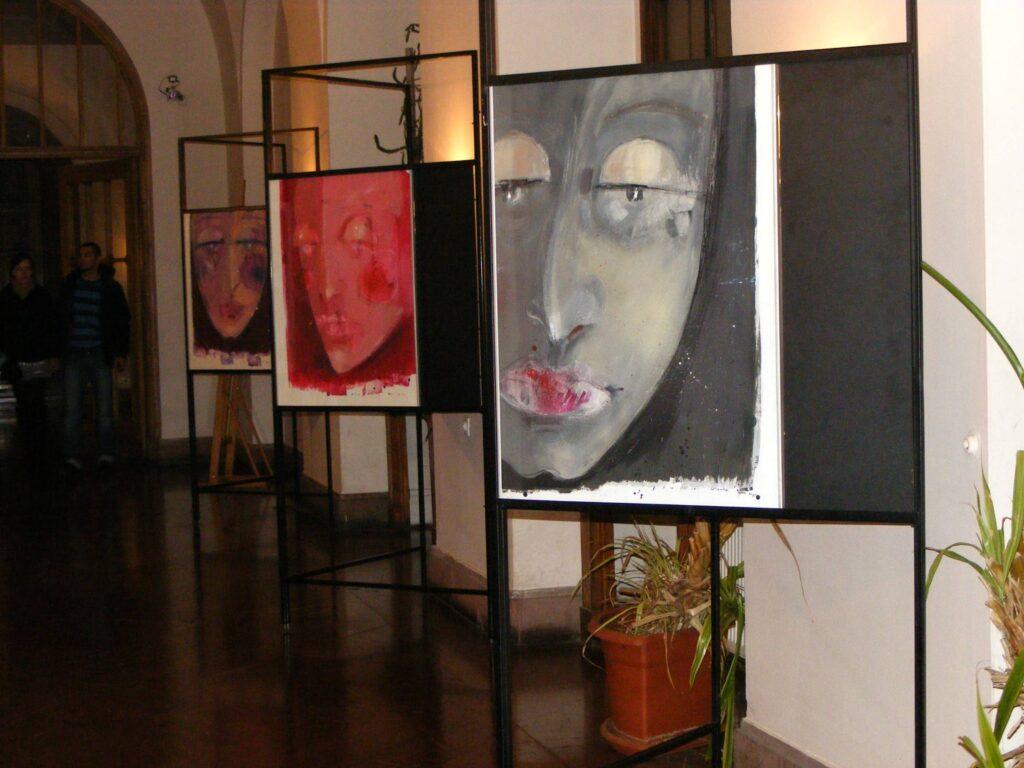 Trzy prace malarskie na stelażach wystawienniczych, przedstawiające twarze w konwencji maski.