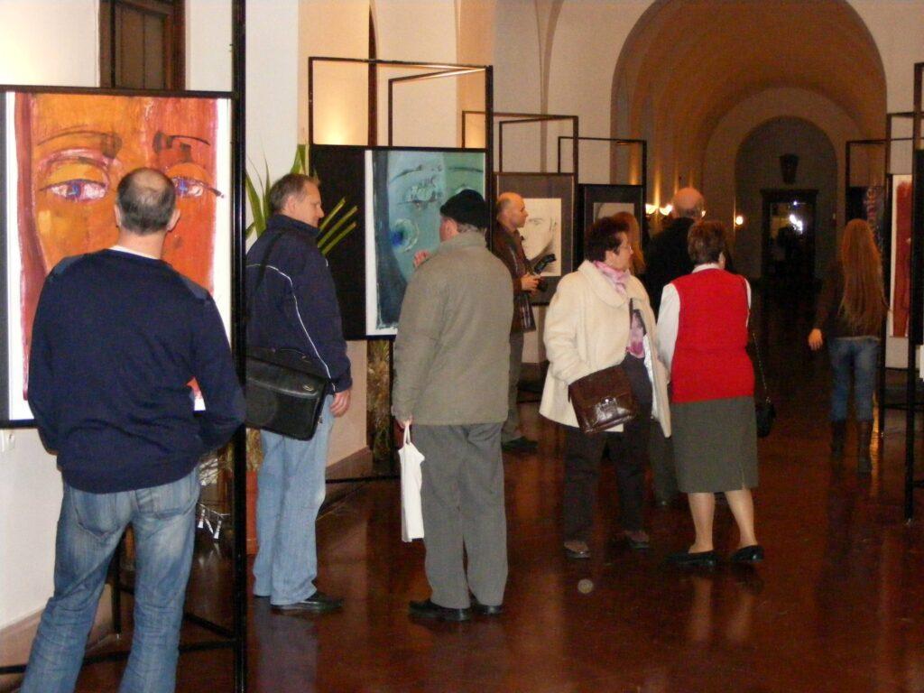 Wernisaż. Wiele osób oglądających i spacerujących pomiędzy prezentowanymi na wystawie pracami.