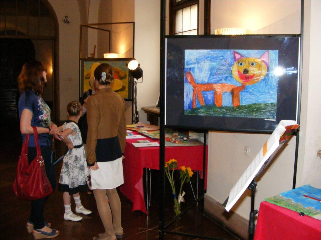 Wystawa prac dziecięcych. Na pierwszym planie rysunek przedstawiający wielkiego kota, dalej, stół z pracami przestrzennymi, którym przygląda się kilka osób.