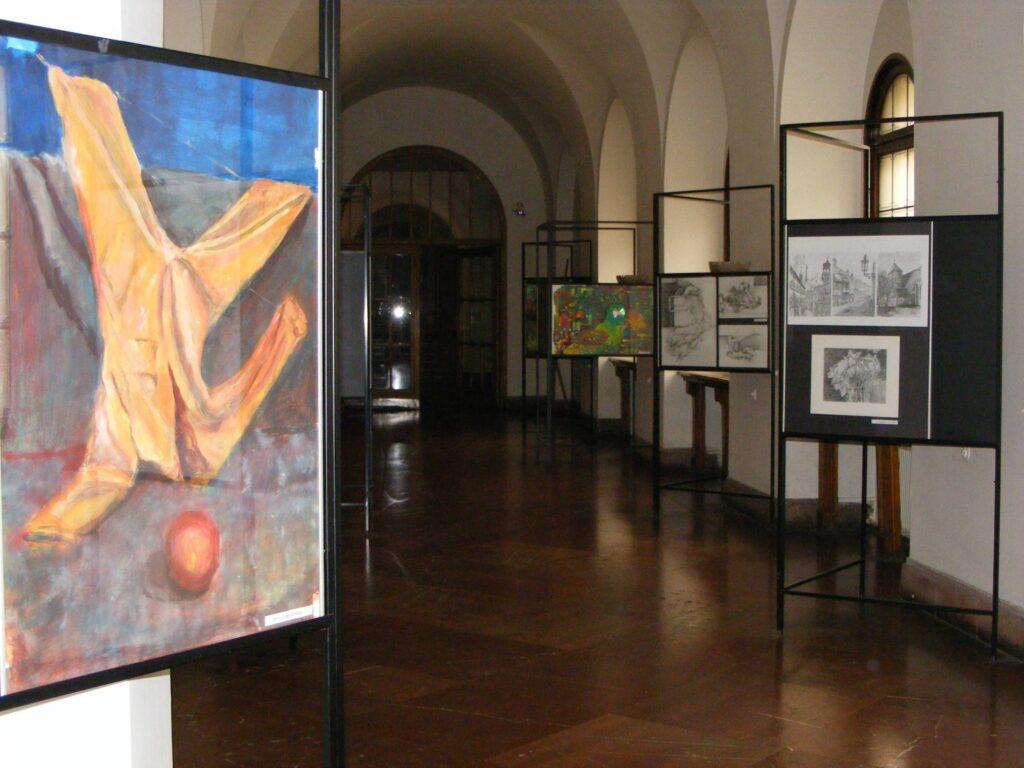 Zdjęcie galerii. Widać w oddali wiele prac i jedną na pierwszym planie, przedstawiającą żółty kombinezon powieszony za nogawki, a przy jego kołnierzu leży pomarańczowa kula.