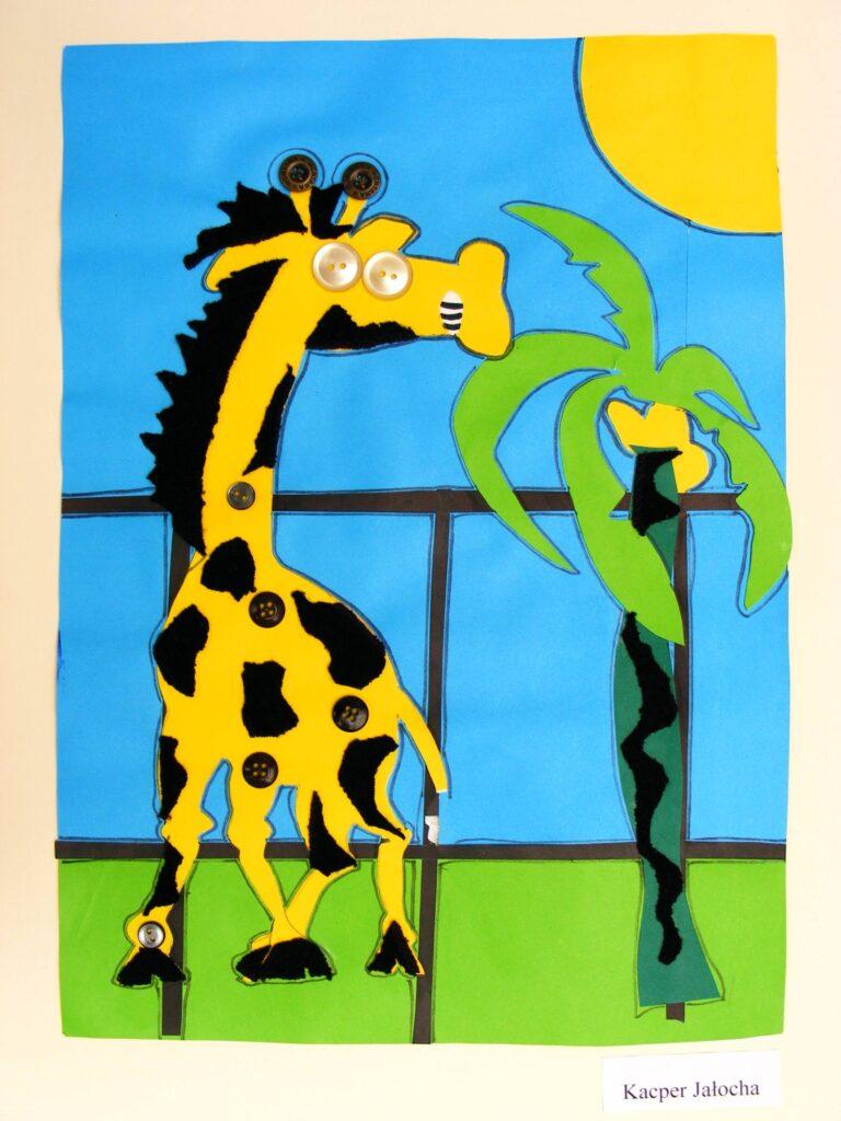 Praca dziecięca, przedstawiająca żółtą żyrafę jedzącą gałęzie palmy na tle błękitnego nieba.