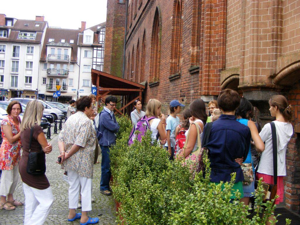 Grupa uczestników pleneru, stojąc na ulicy przed Bazyliką Katedralną, słucha opowieści przewodnika turystycznego.