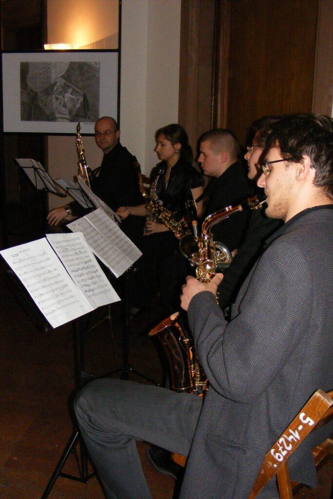Wernisaż w galerii. Pięciu muzyków gra na instrumentach dętych