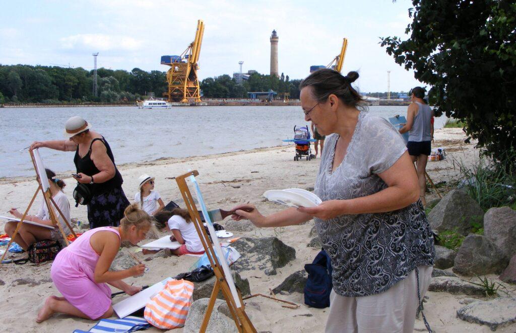 Plaża w Świnoujściu. Dzieci, młodzież i dorośli malują pejzaż, trzymając prace na kolanach lub przenośnych sztalugach. W oddali widać port.