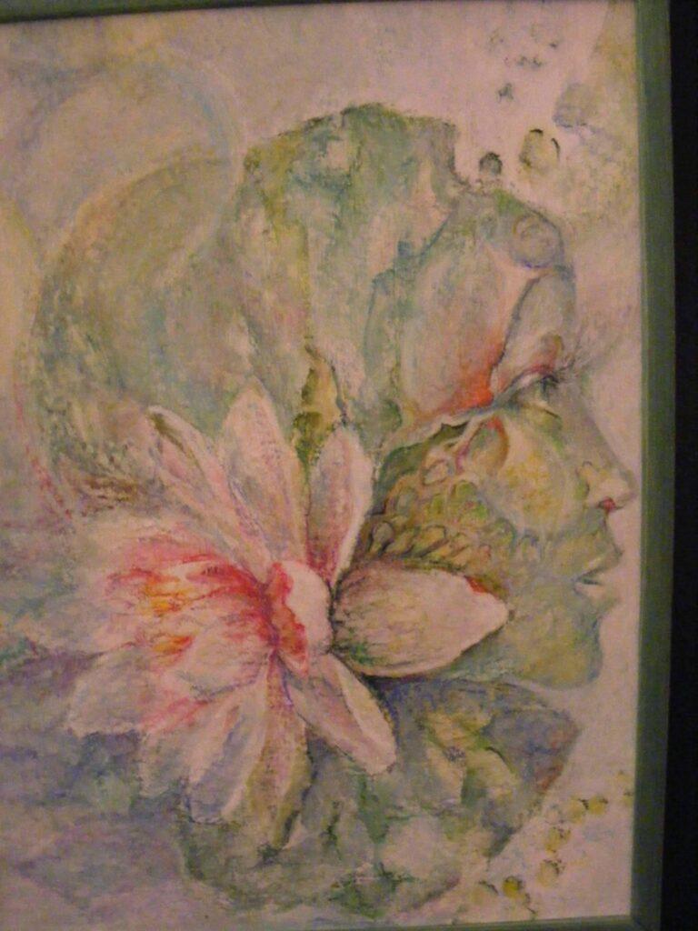 Praca wykonana pastelami, przedstawiająca głowę kobiety ustawioną prawym profilem i ozdobioną przy uchu dużym kwiatem.
