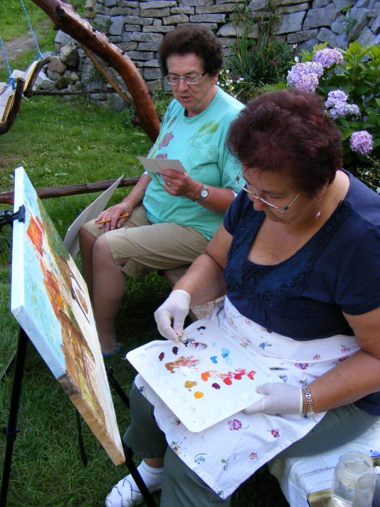 Dwie kobiety siedzące na ławce w ogrodzie. Kobieta na pierwszym planie maluje obraz farbami. Kobieta na drugim planie przygląda się fotografii, którą będzie szkicować ołówkiem.
