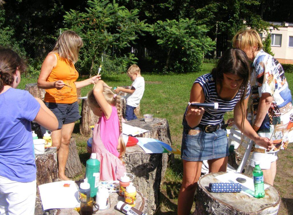 Czworo dzieci i dwie panie malują coś w ogrodzie, a za stoły służą im drewniane pnie.