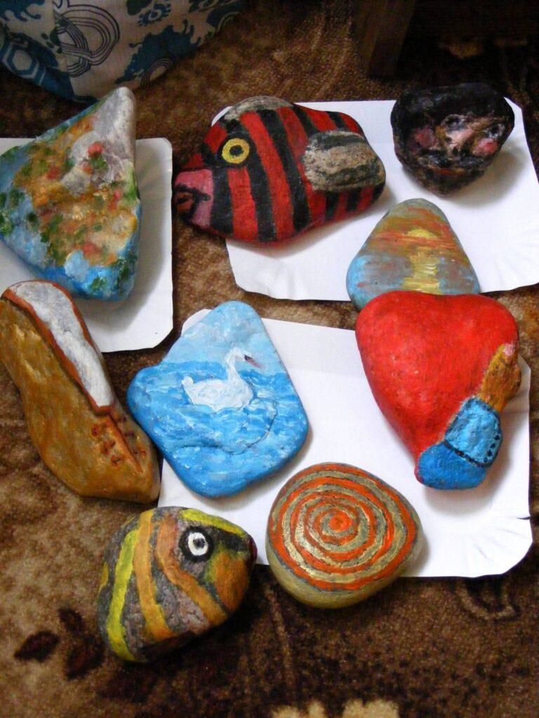 Dziewięć kamieni pomalowanych przez uczestników pleneru. Namalowali pejzaże, ryby, but i łabędzie.