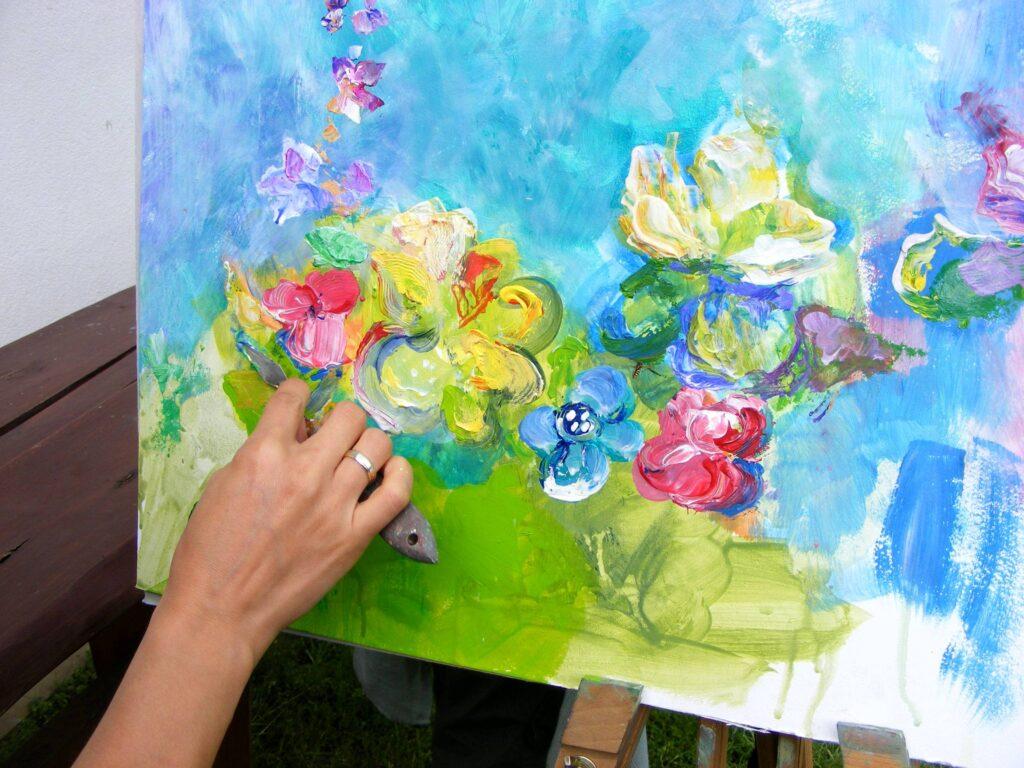 Obraz przedstawiający kwiaty oraz ręka nakładająca na niego farbę szpatułką.