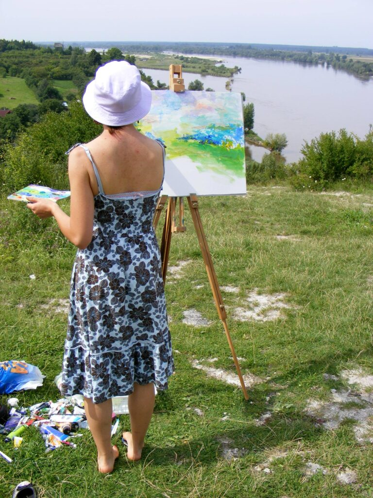Kobieta stojąca tyłem na wzgórzu w Kazimierzu Dolnym. Maluje oparty o sztalugę obraz, na którym uchwyciła koryto Wisły, które widać w oddali.