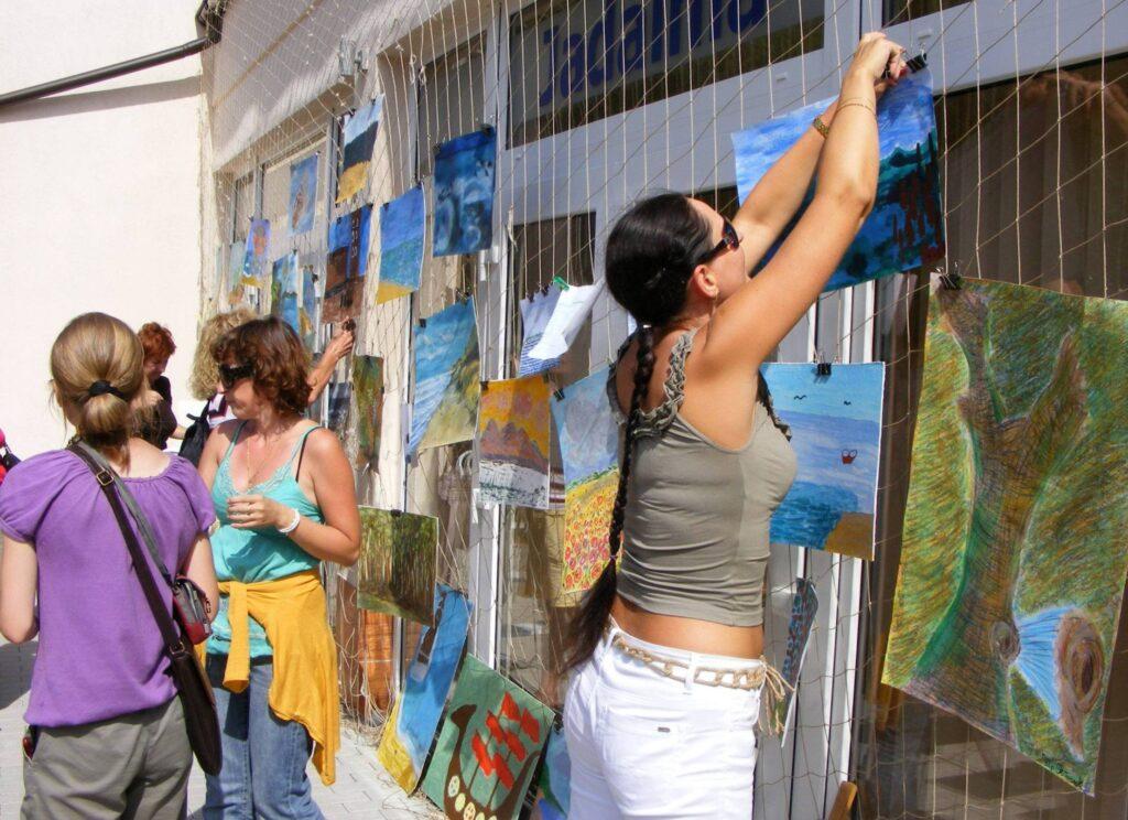 Na oknie jadalni, od zewnątrz rozwieszono siatkę, na której wiszą prace uczestników pleneru w Kołobrzegu. Na pierwszym planie kobieta wiesza kolejną pracę, nieco z tyłu kilka kobiet omawia powieszone prace.