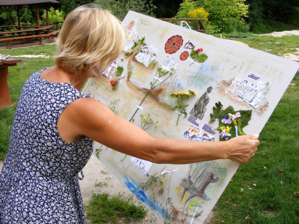 Kobieta stojąca w ogrodzie trzyma planszę z przyklejonymi i namalowanymi wspomnieniami z pleneru. Są na niej: budowle z Kazimierza Dolnego, rośliny, pomnik, wąwóz i inne, mniej widoczne elementy.