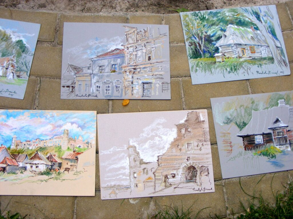 Prezentacja na chodniku sześciu prac wykonanych w plenerze, na których widnieją, kamienice, domy wiejskie, zamek na wzgórzu i ruiny zamku.