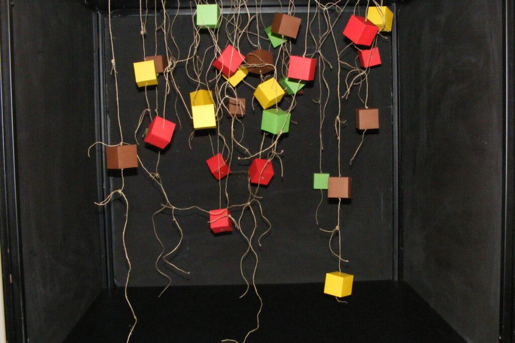 Instalacja przestrzenna – papierowe sześciany powieszone na sznurkach.