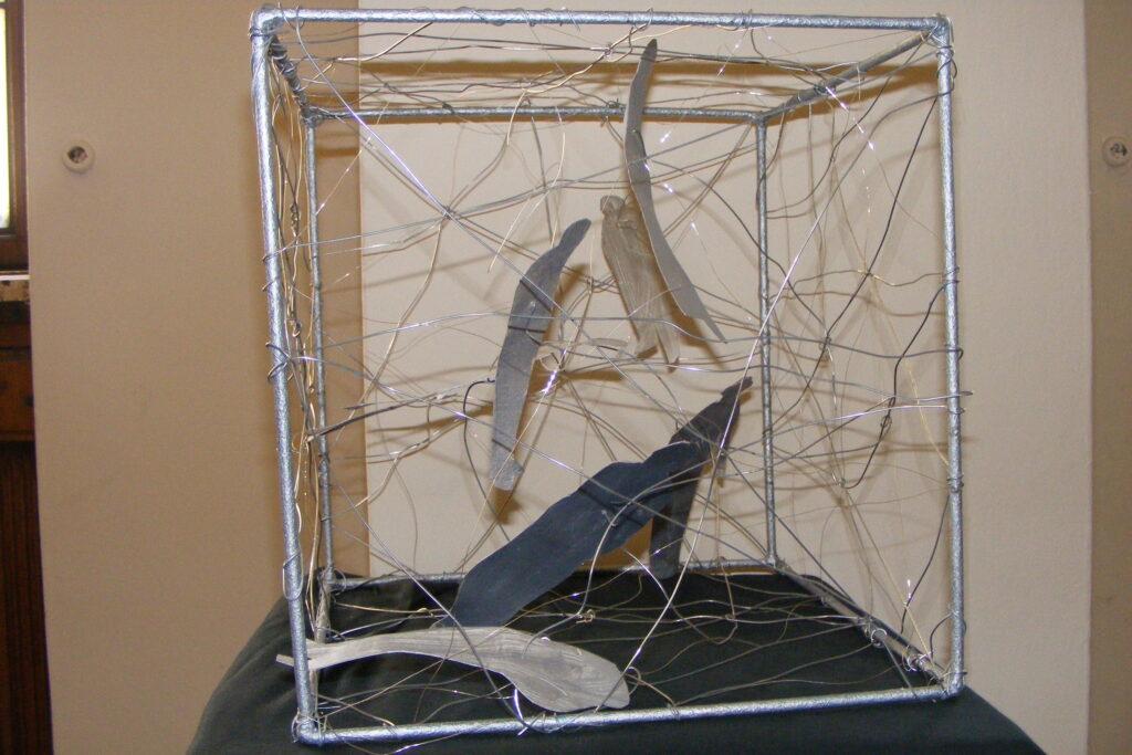 Instalacja przestrzenna – szkielet sześcianu z uwięzionymi w nim sylwetkami ludzi, ściany sześcianu są z drutu.