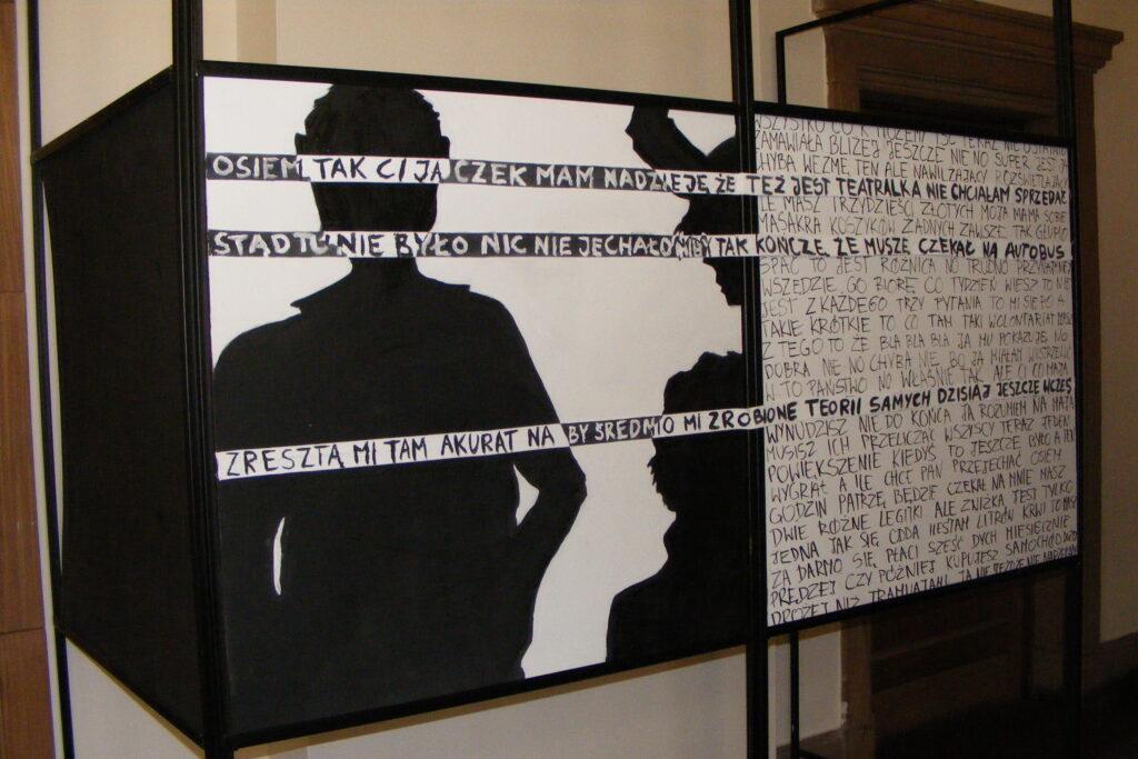 Praca prezentowana na wystawie, przedstawiająca dwie czarne postacie pokryte napisami.