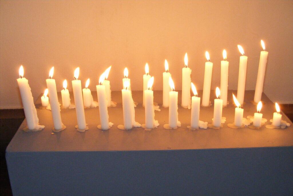 Instalacja przestrzenna – dwa rzędy dwunastu, malejących i rosnących, palących się świec.