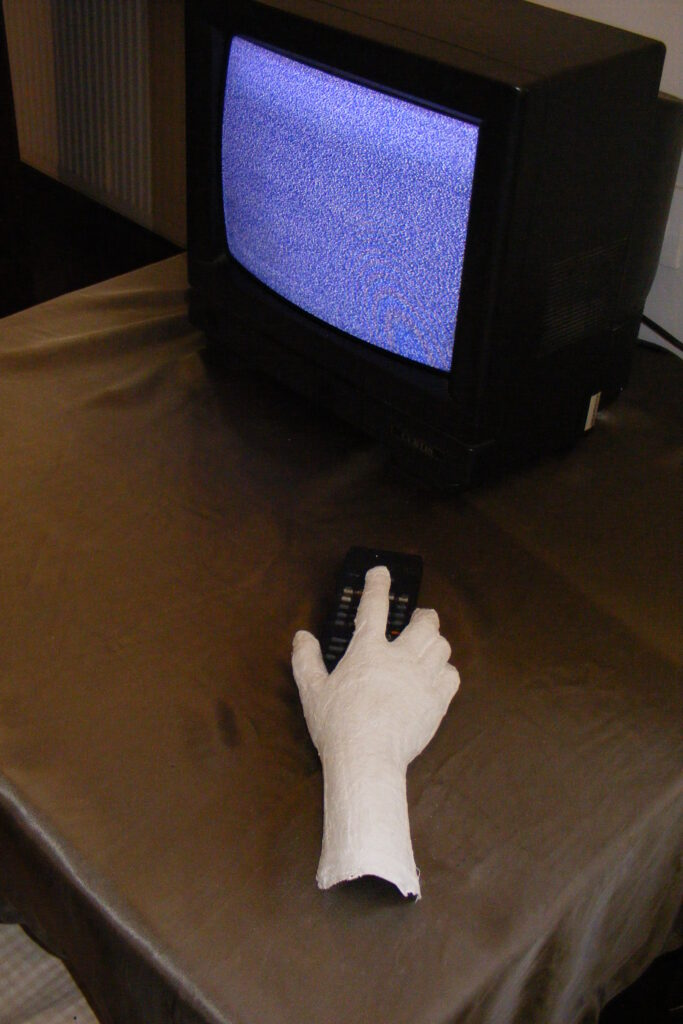 Instalacja przestrzenna – telewizor z niebieskim ekranem oraz gipsowa dłoń trzymająca pilota.