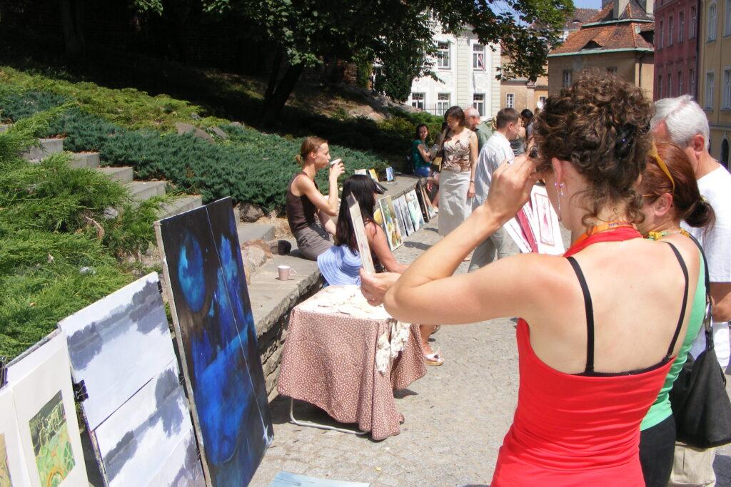 Prezentacja prac uczestników pracowni na Wzgórzu Przemysła. Od lewej: teren zielony na wzgórzu, prace uczestników oparte o murek, przechodnie oglądający obrazy, budynki przylegające do wzgórza.