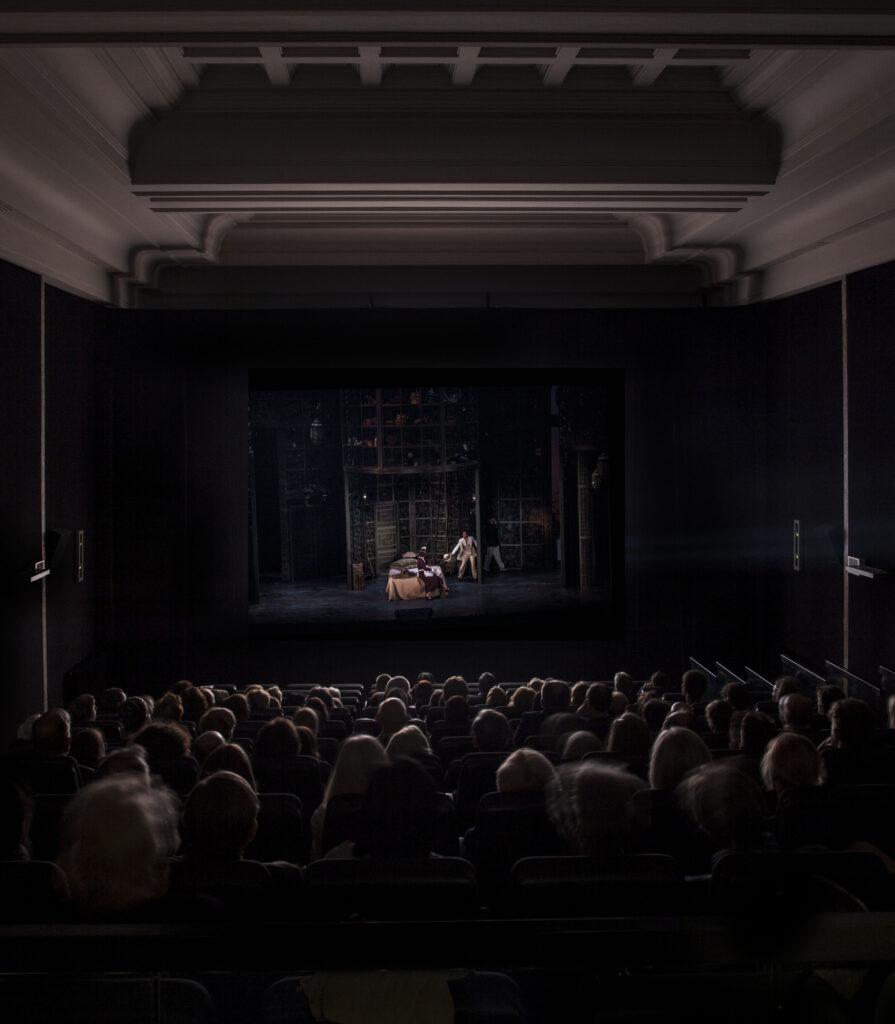 Wypełniona sala kinowa, skąpana w czerni. Widoczne rzędy głów widzów oświetlonych światłem z ekranu. Na ekranie przedstawienie teatralne.