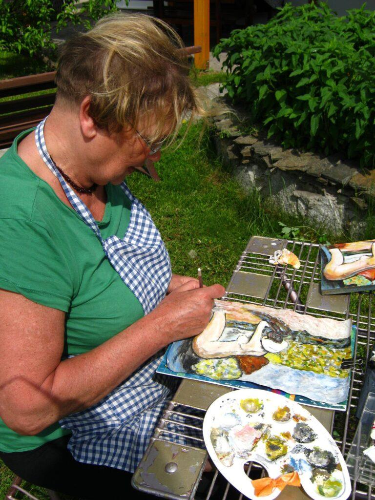 Siedząca w ogrodzie uczestniczka pleneru maluje przy ogrodowym stole, na którym poza pracą leży też paleta z farbami